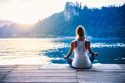 Young woman meditating by the lake