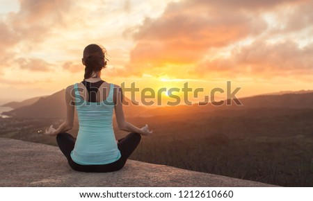 Young woman meditating from a mountain top facing beautiful sunset. Healthy mind and body. #1212610660