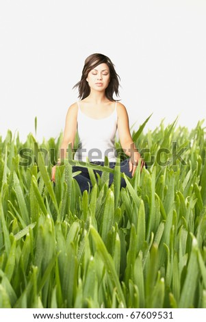 Young woman meditating in tall grass