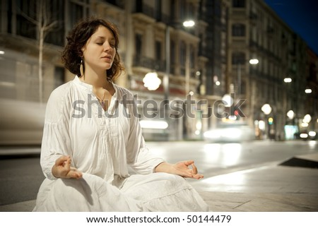 Young woman meditating in the city in a long exposure shoot with blurred traffic.