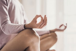 Young woman meditating in the lotus pose at home. Fit girl doing exercises, practicing yoga indoors. Harmony, yoga practice, balance, meditation, relaxation at home, healthy lifestyle concept