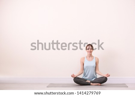 Young woman meditating near light wall, space for text. Zen concept Foto stock ©
