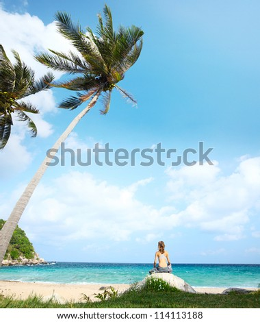 Young woman meditating on a tropical beach - stock photo