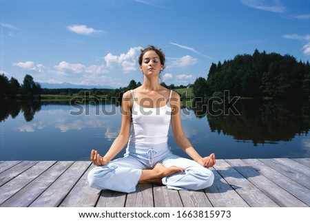 Young woman meditating on dock