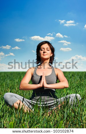 young woman meditating on the field at sunny day