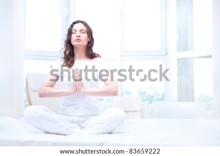 Young woman meditating with closed eyes in bright bedroom sitting on bed