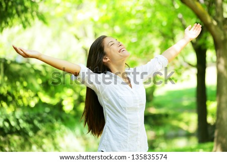 Young woman meditating with open arms standing in fresh spring greenery with her head raised to the sky and her eyes closed rejoicing in the freshness and new beginnings of spring and nature