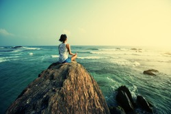 Young woman meditation on seaside rock cliff edge
