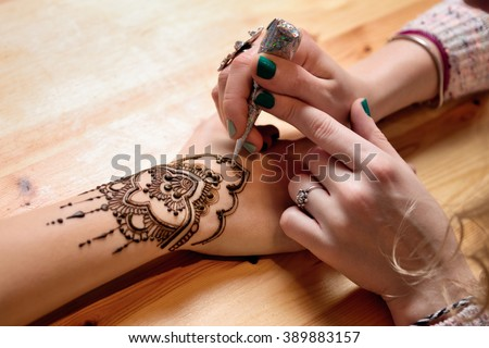 young woman mehendi artist painting henna on the hand Stock photo ©