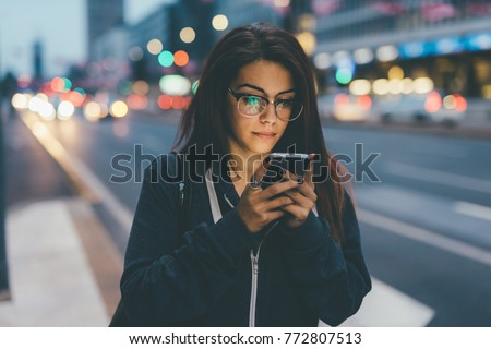 young woman mixed race outdoor night using smart phone face illuminated by screenlight - internet, social network, technology concept