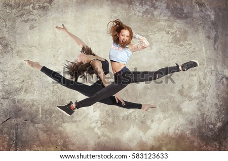 Young woman modern ballet dancing on wall background