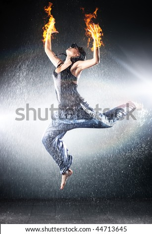 Young woman modern dance. Water studio photo and fire effect.