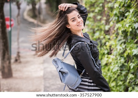 Young woman moving her hair in urban background wearing leather jacket #357527900