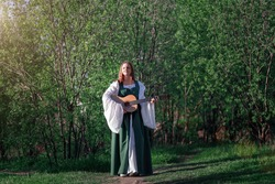 Young woman musician in medieval long dress walks with guitar in sunny summer green forest. Fantasy girl or bard at summer nature.