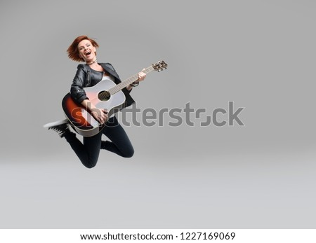 Young woman musician with an acoustic guitar in hand jumping high on a gray background. He laughs and plays rock and roll loudly.