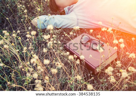 young woman napping on the dandelion field after reading book put out glasses on the book