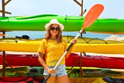 Young woman near kayaks at sunny day. Summer holiday and vacation concept