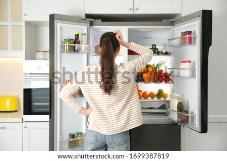 Young woman near open refrigerator in kitchen, back view