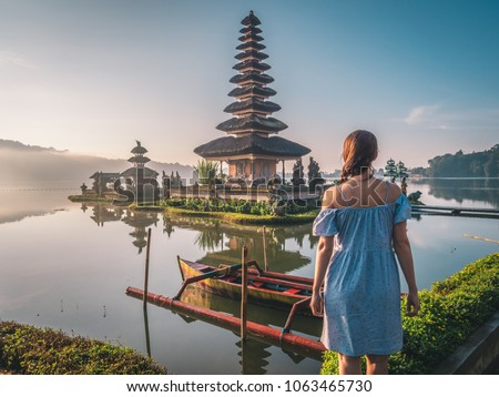 Young woman near Pura Ulun Danu Bratan temple near Beratan lake in Bali island, Indonesia at sunrise. Iconic image of Bali and southeast asia. Travel and adventure background image.