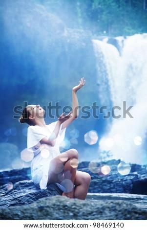 Young woman near waterfall, bali, indonesia