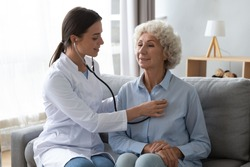 Young woman nurse doctor gp holding stethoscope examining old senior 60s grandma patient check heartbeat at homecare checkup medical visit at home hospital, older people cardiology healthcare concept