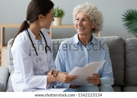 Young woman nurse doctor wear medic uniform consult happy old grandmother patient hold papers show medical test result offer healthcare consent insurance contract form at home hospital concept