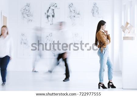 Young woman observing sculpture in modern art gallery with drawings. Art gallery concept  #722977555