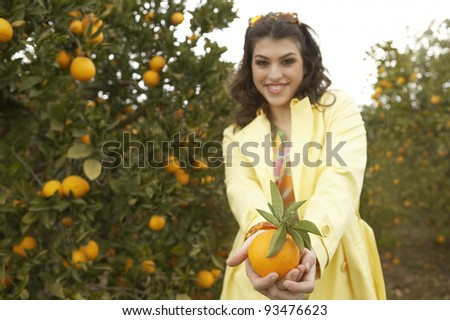 Young woman offering a fresh orange to the camera while standing in an orange grove.