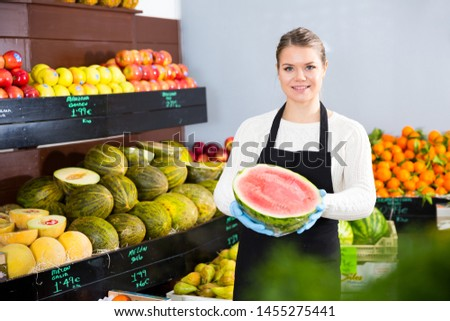 Young woman offering watermelon and other fresh fruits on the market