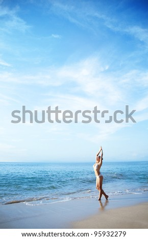 Young woman on a beach doing yoga