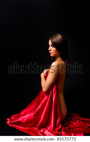Young woman on a black background nude covering her front with a sheet of red satin in profile with her back exposed