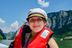 Young woman on a boat enjoying an adventure on a river with beautiful mountain in the background.