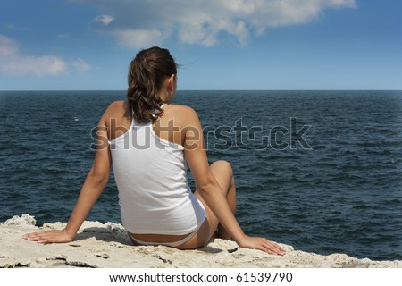 Young woman on a cliff looking at sea