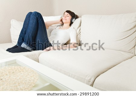Young woman on a couch listening to music with headphones