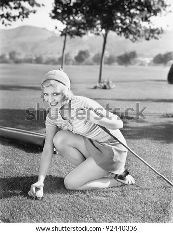 Young woman on a golf course placing a golf ball