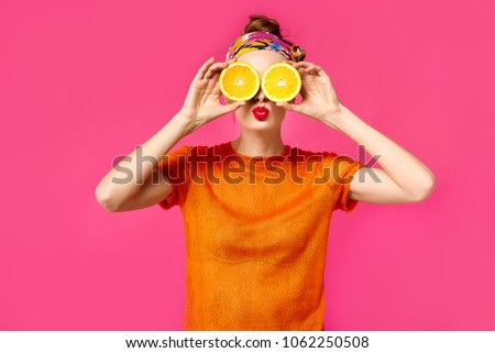 Young woman on a pink background holds a cut orange in her hands and laughs. Colour obsession concept.  Minimalistic style. Stylish Trendy #1062250508