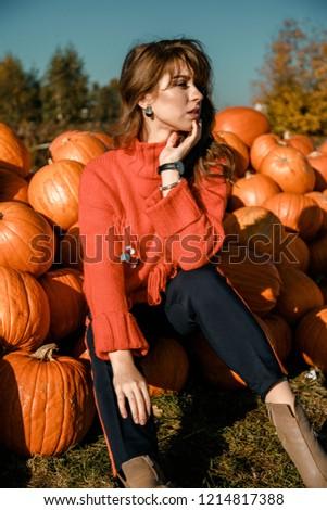 Young woman on a pumpkin farm. Beautiful girl near pumpkins. A girl with a pumpkin