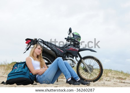 young woman on a road-trip with her motorbike resting on the beach