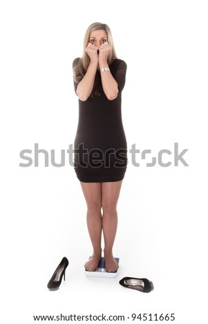 young woman on a scale in  horror under the white background