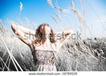 Young woman on a summer field. Infra-red photo effect. - stock photo