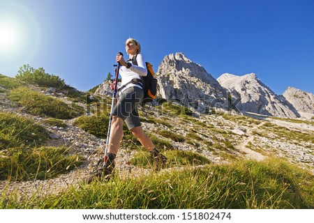 Young woman on a sunny day hiking in high mountains