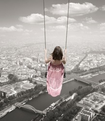 Young woman on a swing on the Paris town background.