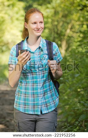 Young woman on a treasure hunt, also known as geocaching in a summer forest.
