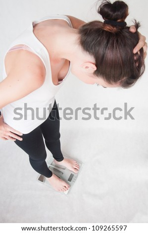 young woman on a weighing scale