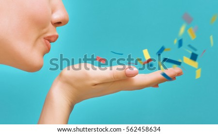 Young woman on background of bright blue wall. Girl blowing multicolor confetti. Close up. Foto stock ©
