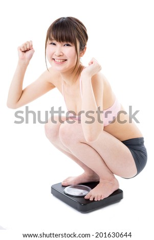 young woman on bathroom scale, isolated on white background