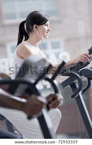 Young woman on bike at gym, exercising and listening to music