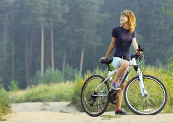 Young woman on bike standing on road and looking to somewhere