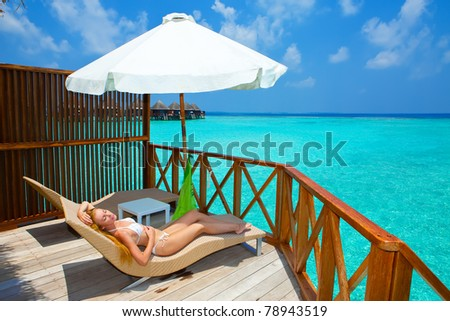 Young woman on chaise lounge under parasol near the sea. Maldives.