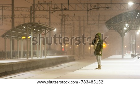 young woman on empty railway platform in blizzard waiting for a train / girl missed a train / woman is waiting for the train in bad weather and talking on the phone
